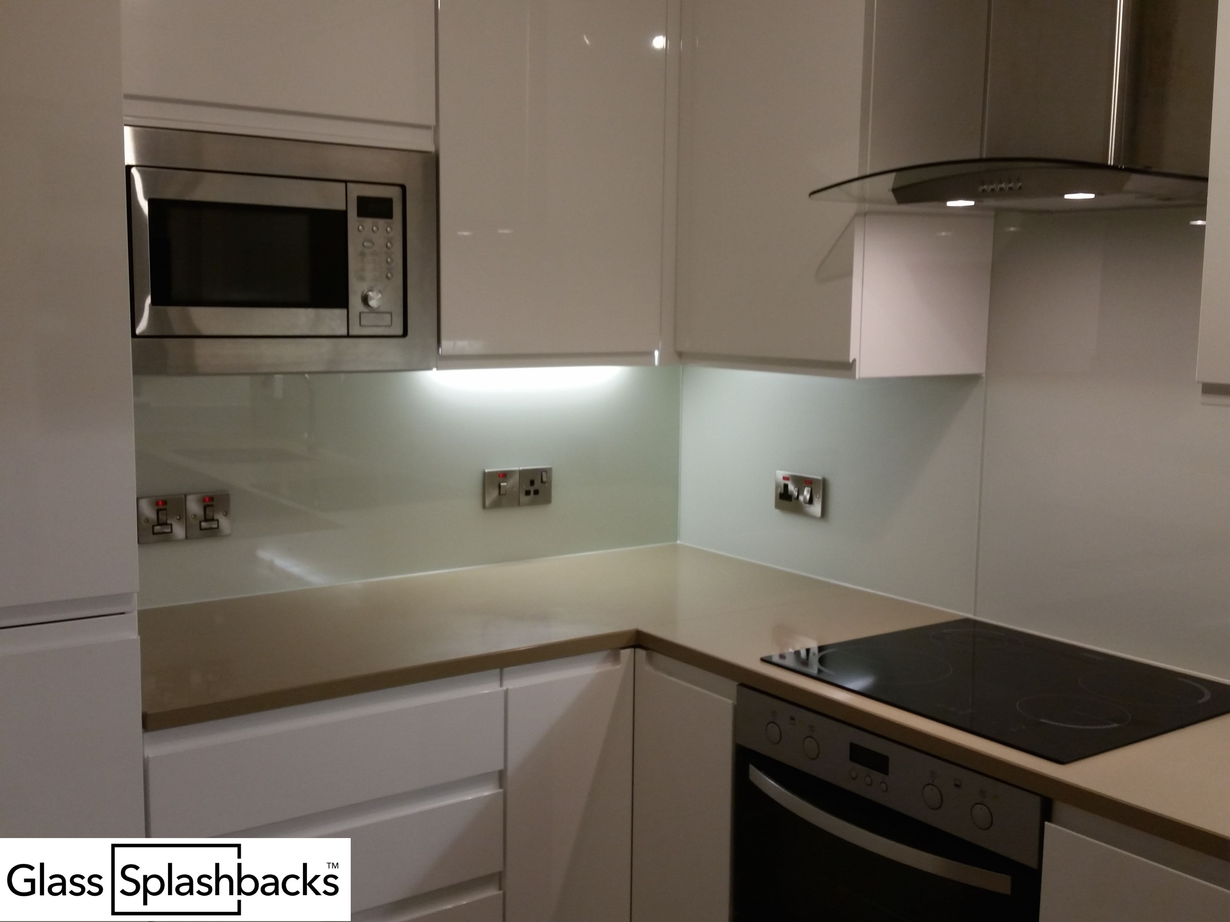 Fully fitted white glass splashback. Shaped around cooker