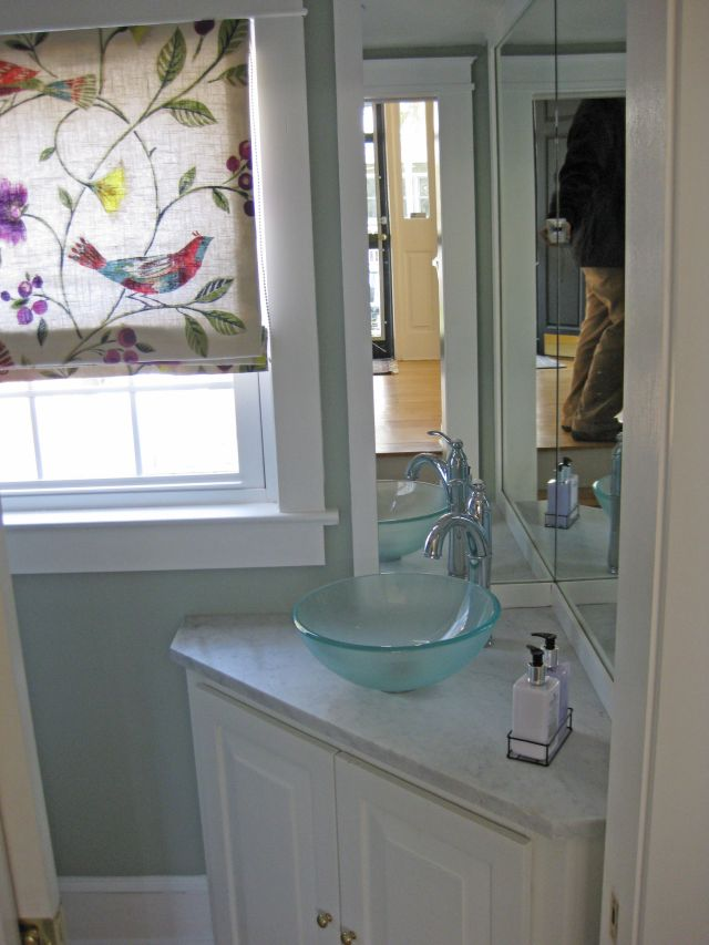 Small powder room bathroom with corner vanity cabinet mount on