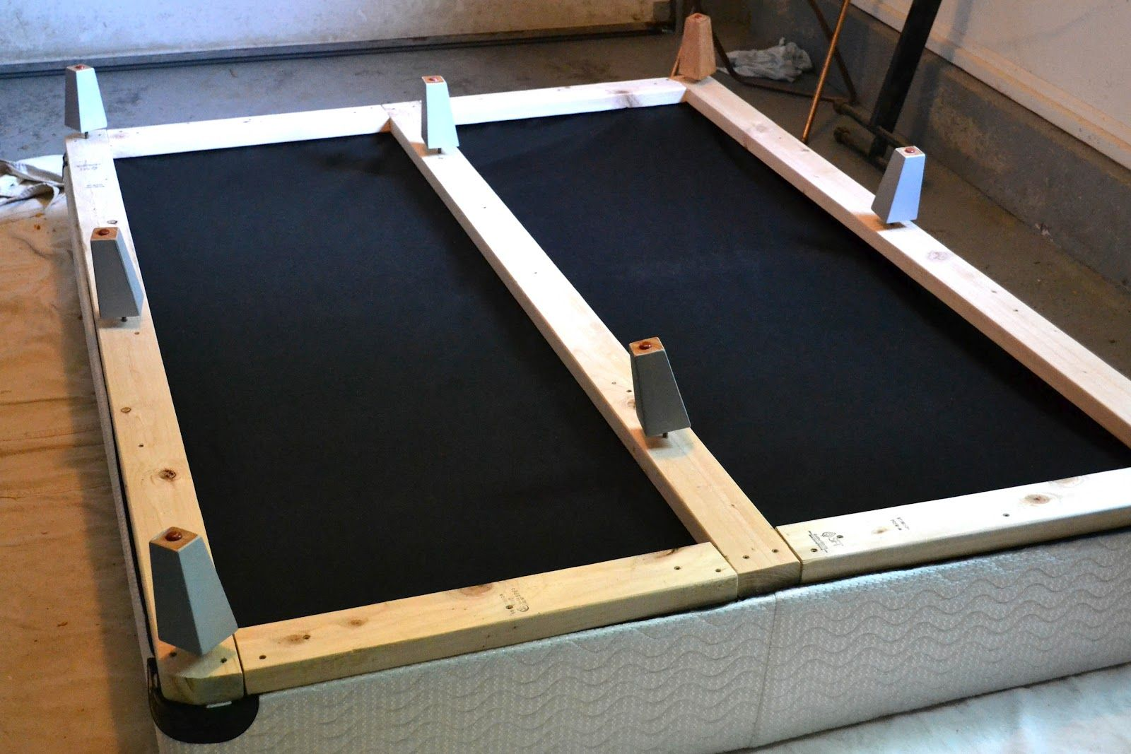 Add boards to bottom of box spring, cover in fabric, and
