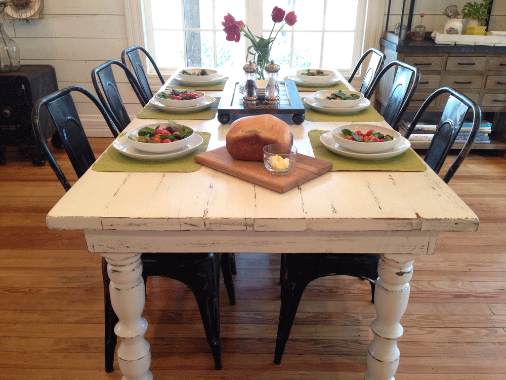 Love this white distressed farm table with the black metal