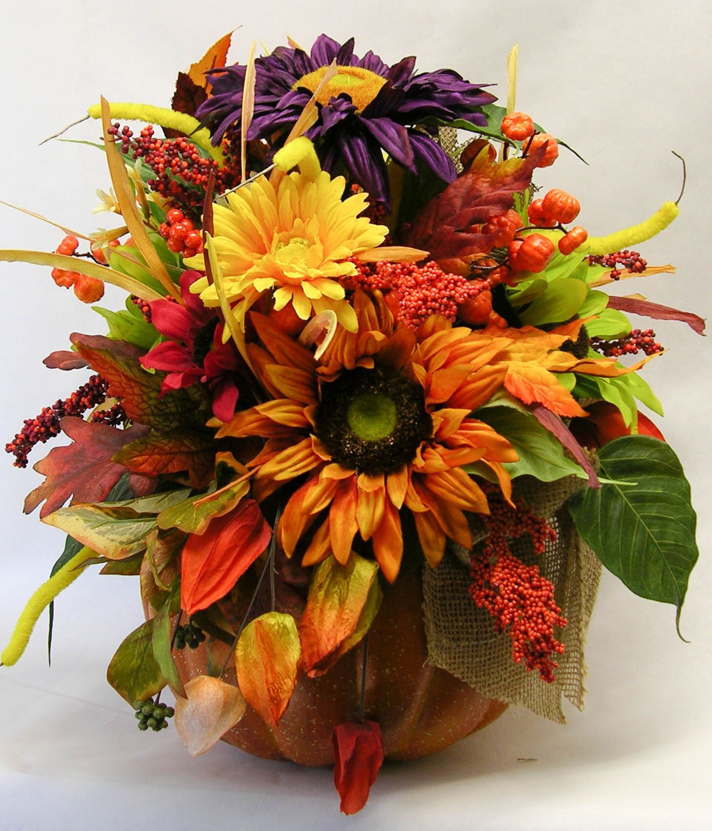 A foam pumpkin filled with sunflowers, leaves and grasses