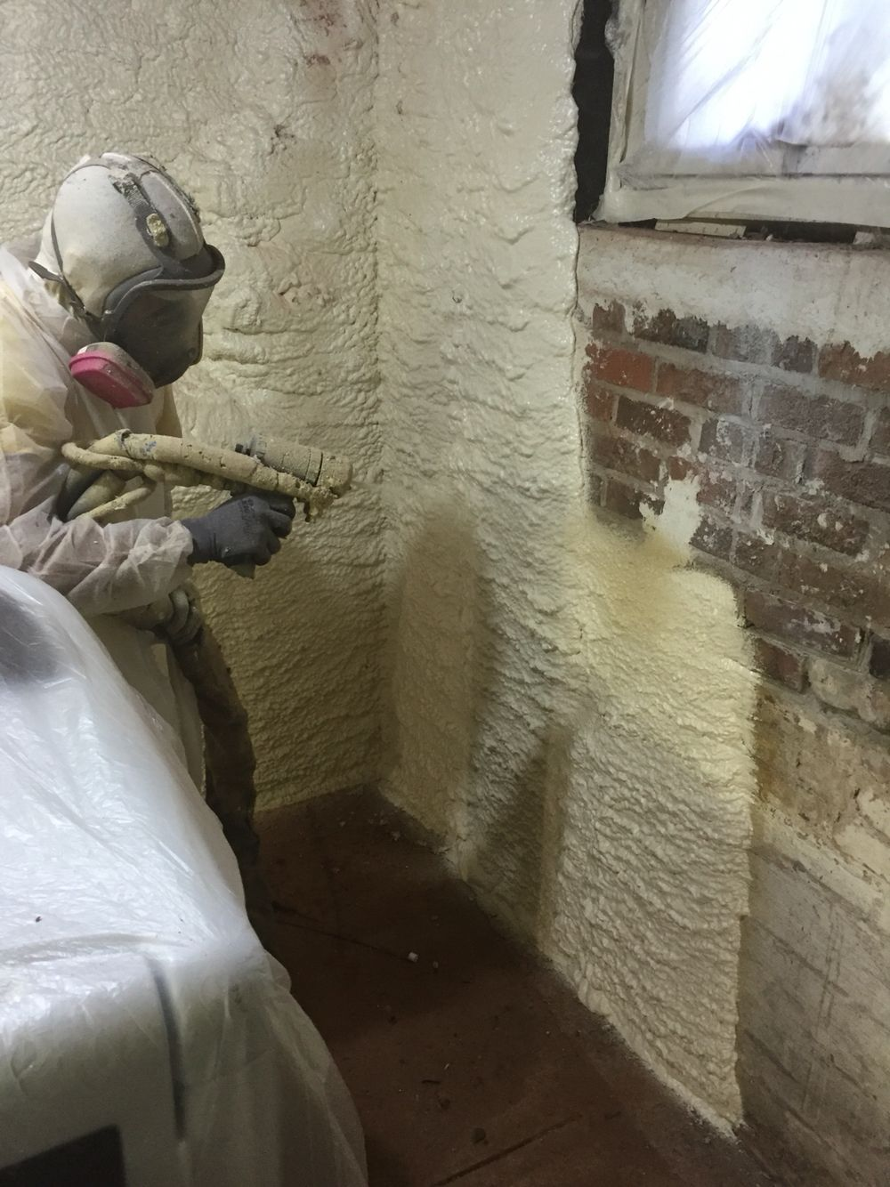 Spraying closed cell foam insulation on the basement walls
