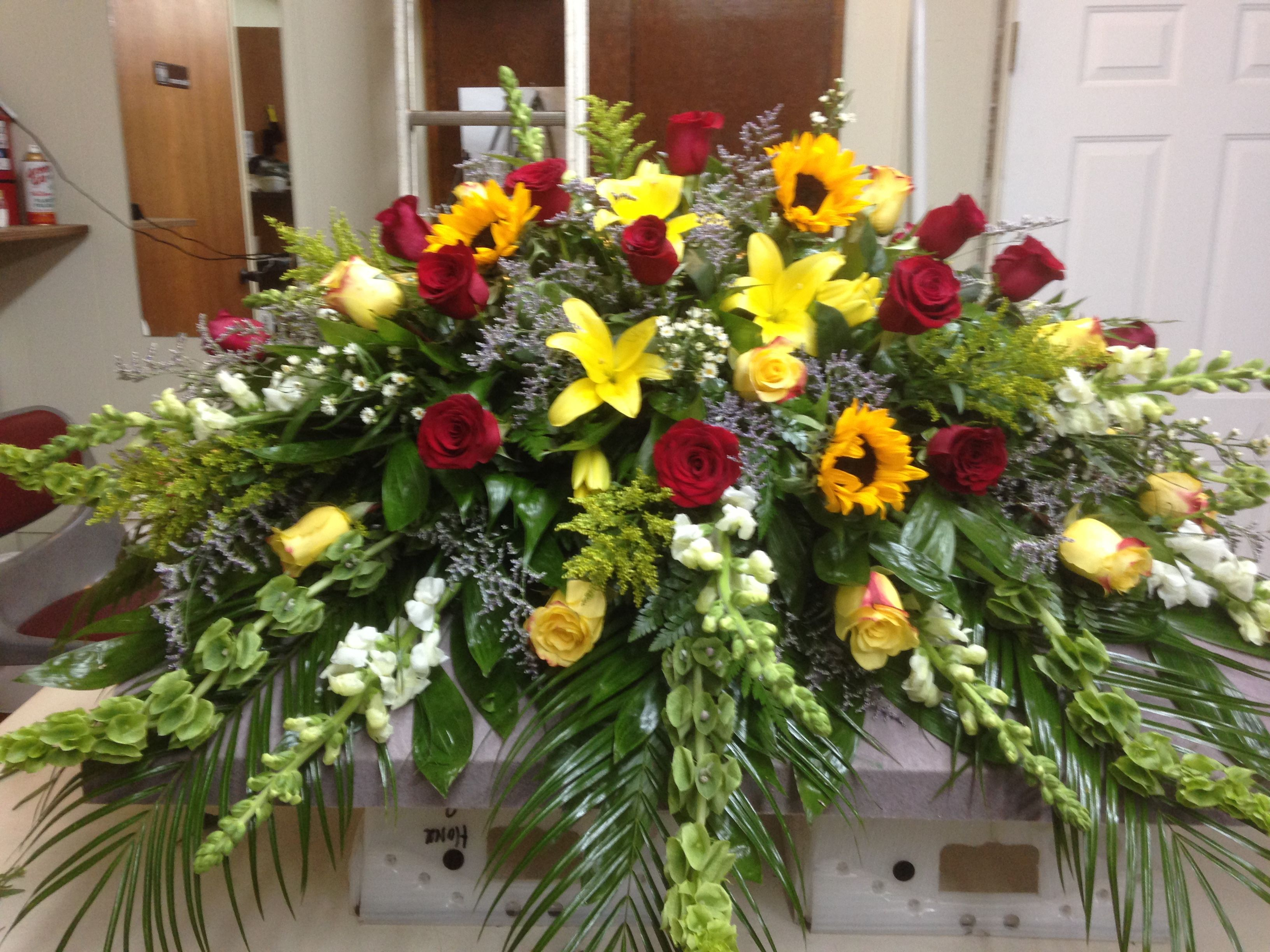 Casket Spray using yellow lilies, yellow roses, red roses