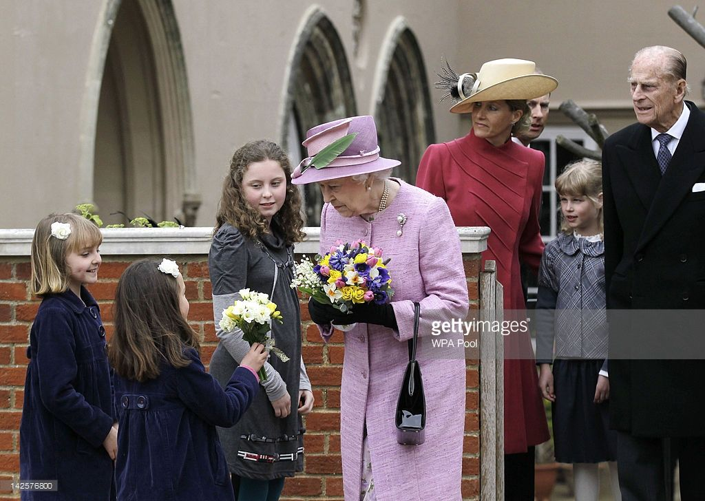 Queen Elizabeth II receives flowers from young well