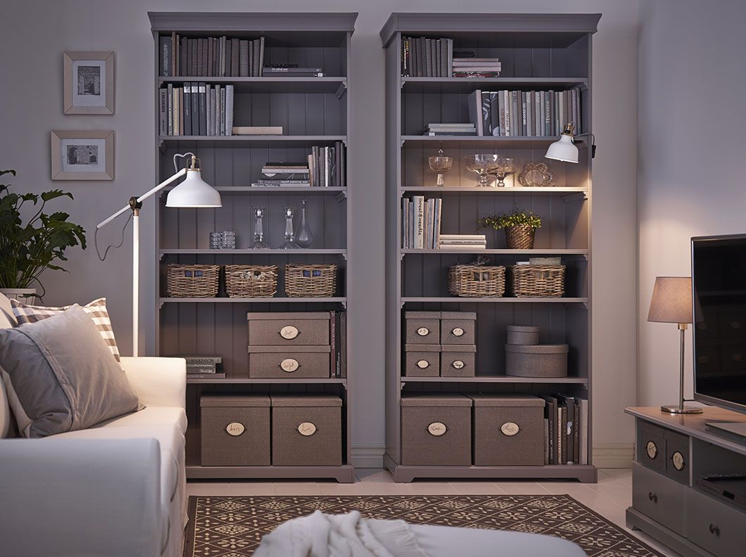 A Living Room With Two Grey Ikea Hemnes Bookcases Filled