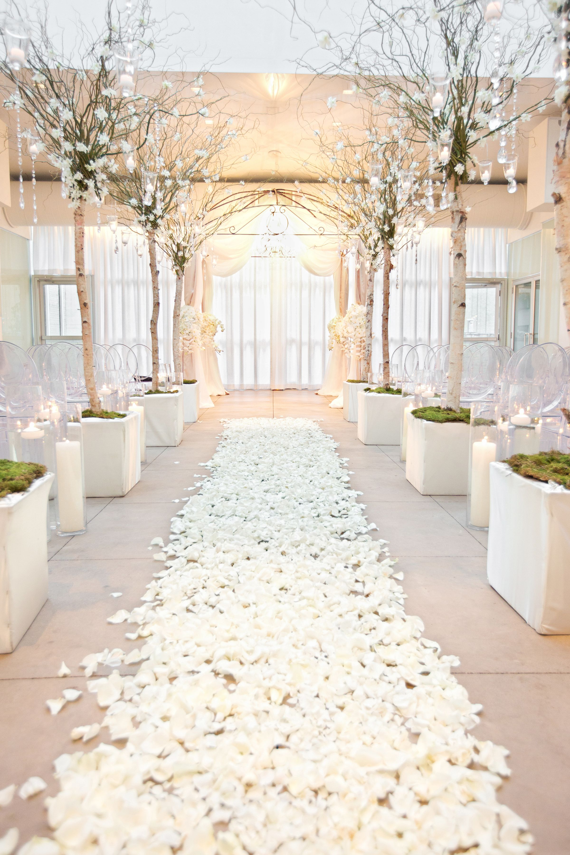 An aisle of white rose petals and branches dripping with