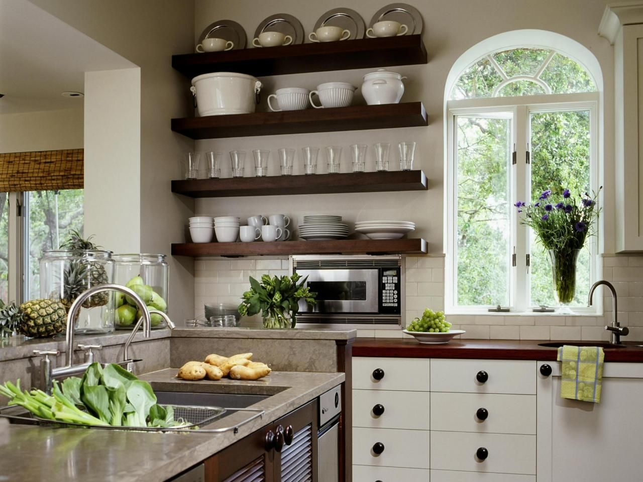 Floating shelves used to store dishes and a large window