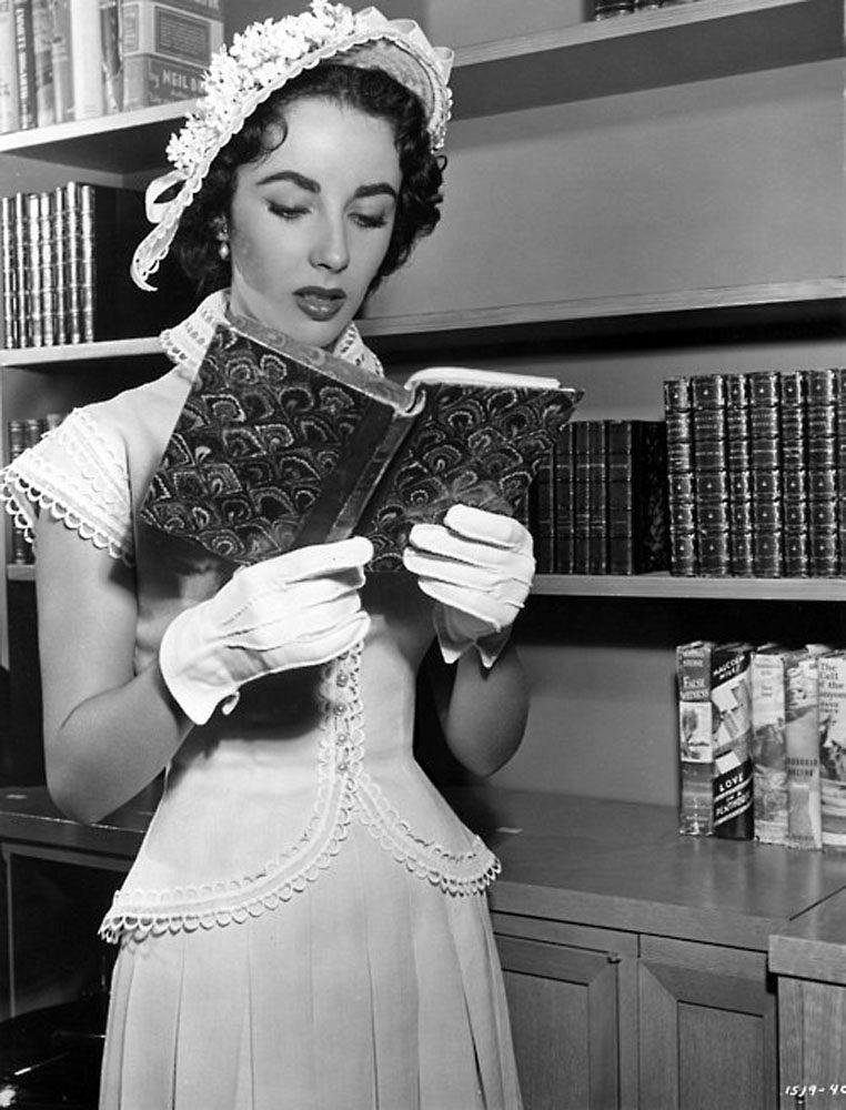 Elizabeth Taylor reading in library. 1950s. Elizabeth