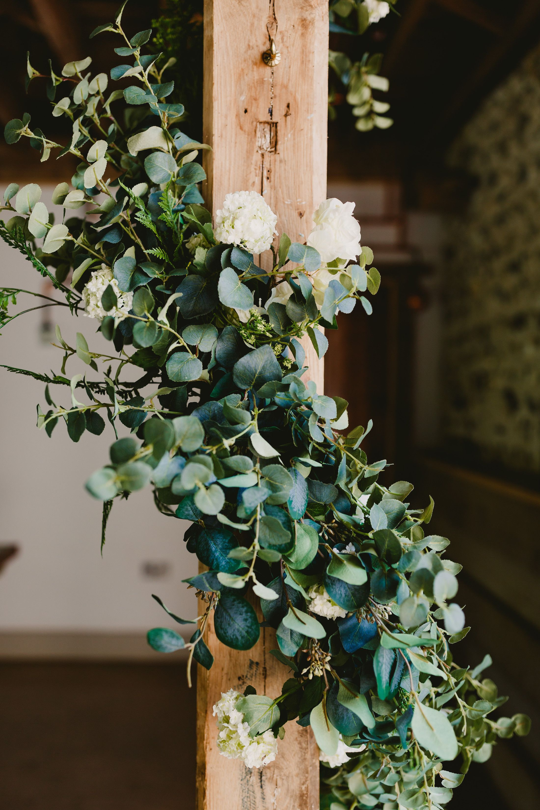 Faux greenery wrapped around a beam for a barn wedding