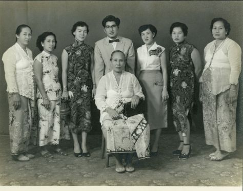 Part of my grandmother's family, consisting of my great-grandmother (front and center), my grandmother (second-right) and her sisters, sisters-in-law, and her brother. Although this picture was taken in the 1950s, you can see that some of the nyonyas still wear more traditional sarong-kebaya outfits (left, right & center), complete with slippers and silver belts.