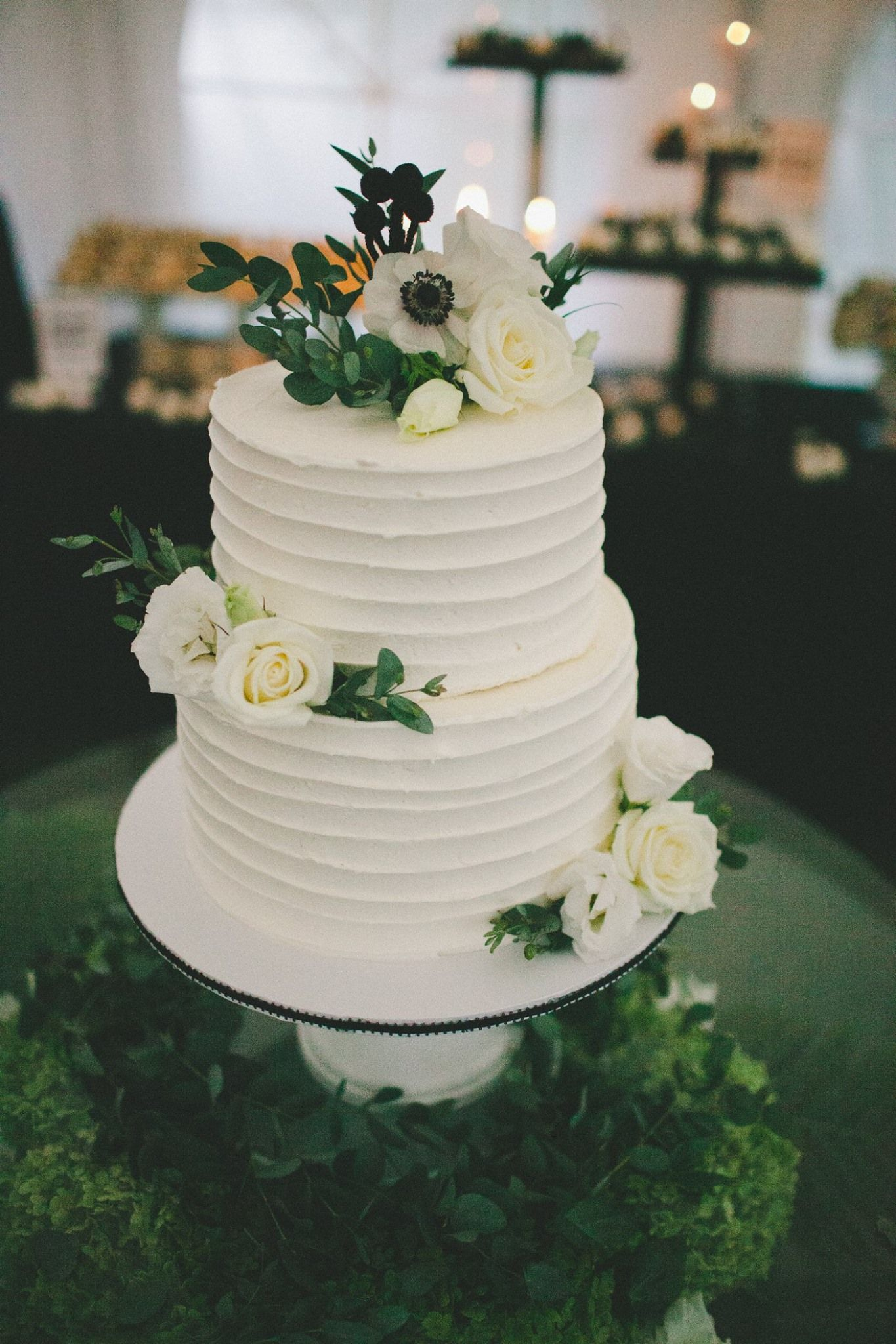 Simple twotier wedding cake covered in real blossoms and