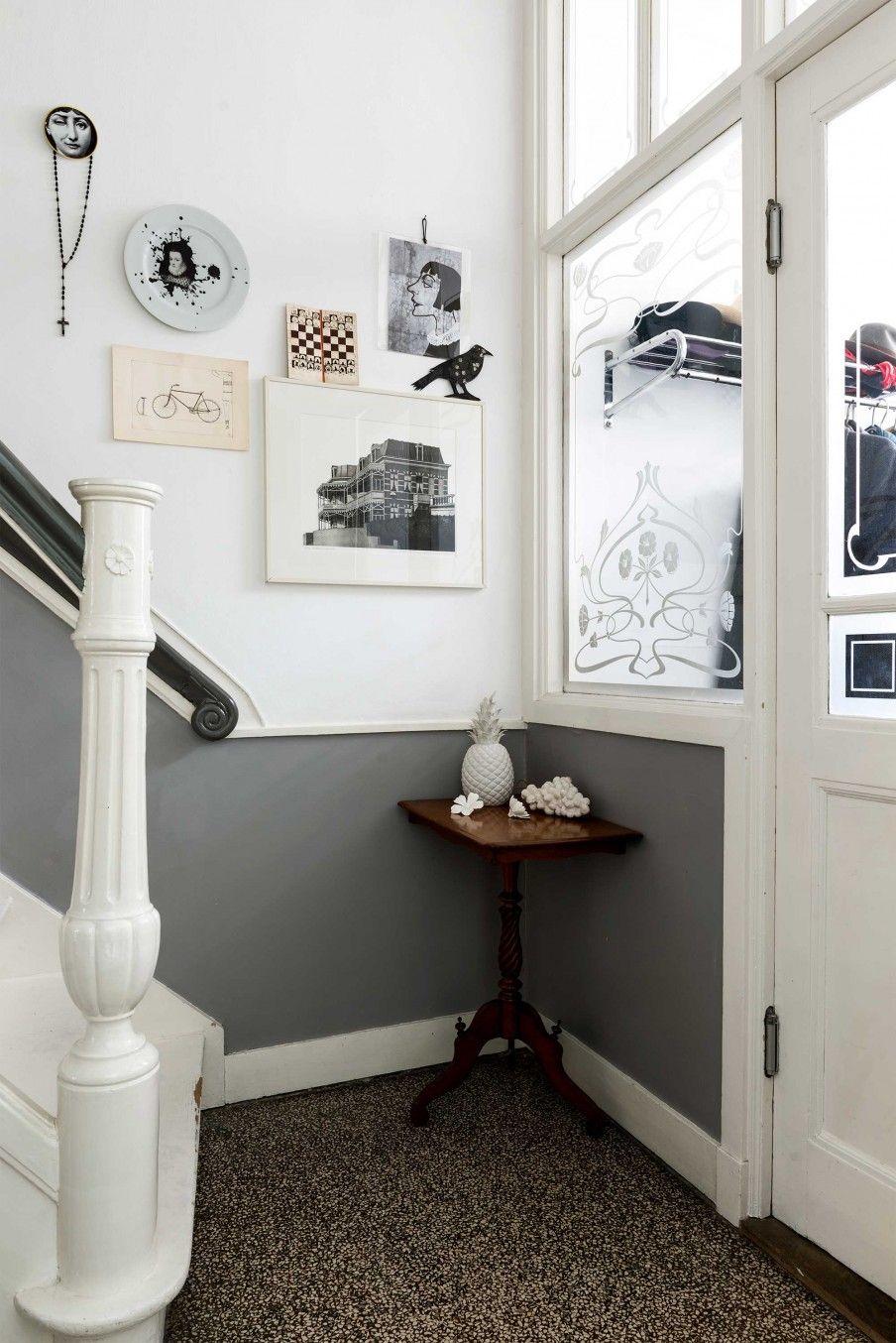 Hal met grijze lambrisering en posters aan de muur Hall