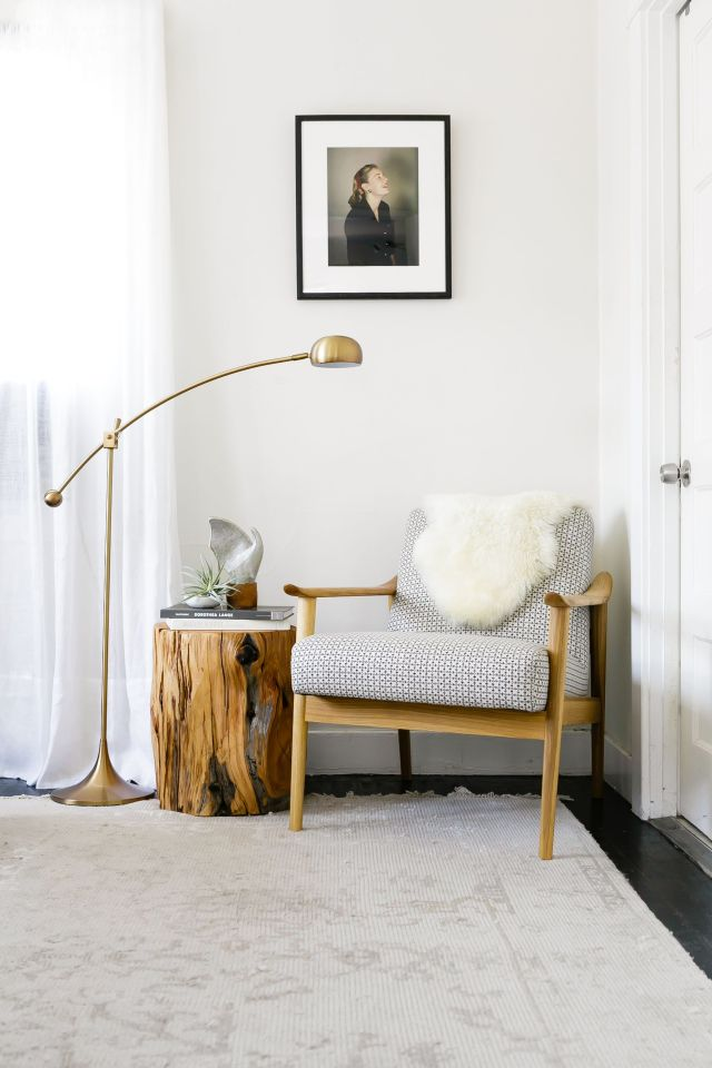 warm modern reading nook with brass lamp and midcentury chair via