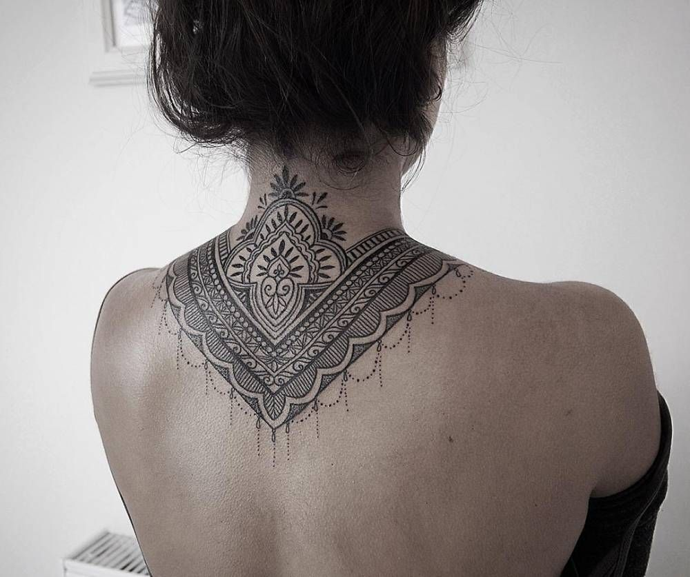 Ornamental style tattoo covering back of the neck and