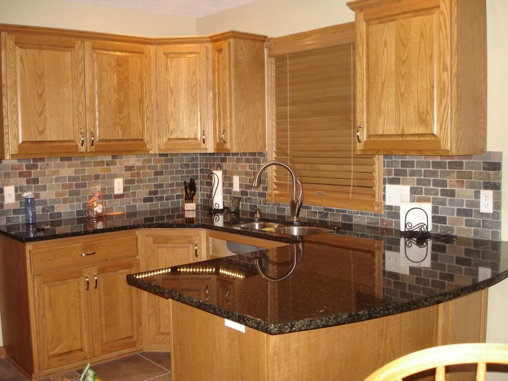 honey oak kitchen with black countertops