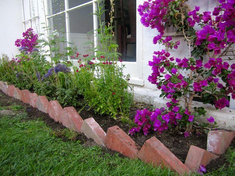 Bricks set on angle as garden border. Toilin' in the