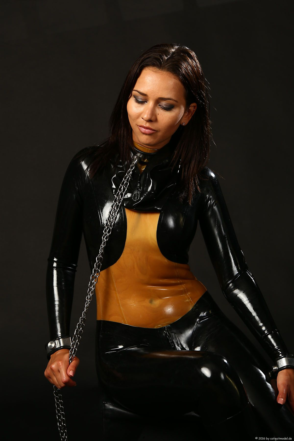 Woman in latex catsuit looks not sad being chained