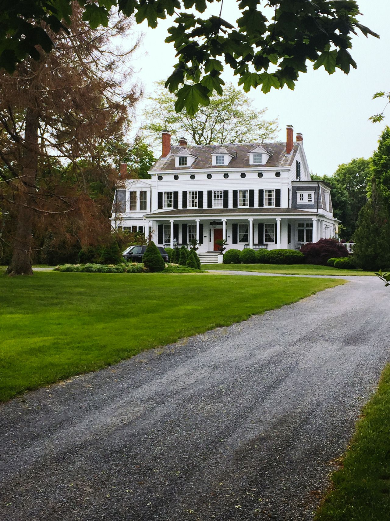 long gravel driveway, big front lawn, white colonial home
