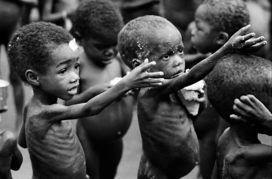 Black and white image of severely malnourished African children begging for food