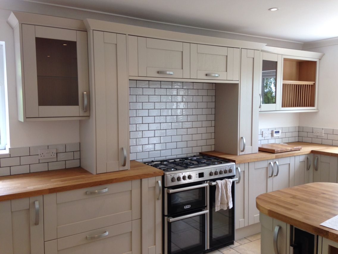 Grey coloured kitchen with solid oak worktop and white