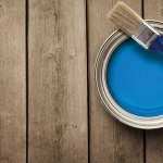 A quart of bright blue paint on a prepped wooden deck.