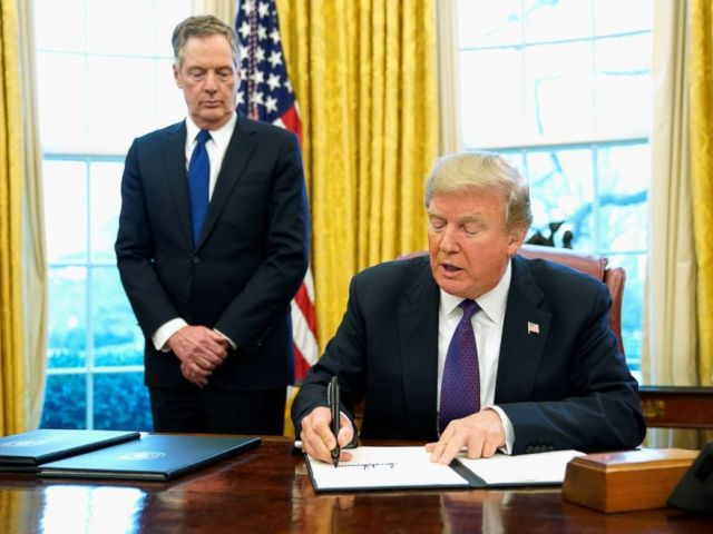 PHOTO: President Donald Trump, flanked by U.S. Trade Representative Robert Lighthizer, signs a directive to impose tariffs on imported washing machines in the Oval Office at the White House in Washington, D.C. Jan. 23, 2018.