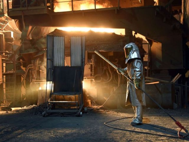 PHOTO: A steelworker in a protective suit checks the temperature of molten metal in furnace at the TMK Ipsco Koppel plant in Koppel, Pa., March 9, 2018.