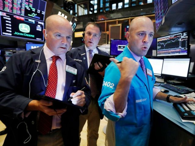 PHOTO: Traders Patrick Casey, left, and Jonathan Corpina, center, work with specialist Jay Woods on the floor of the New York Stock Exchange, Aug. 14, 2019.