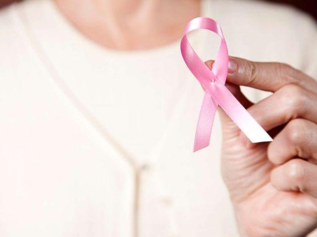 PHOTO: Dans cette photo non datée, une femme portant un chandail rose tenant un ruban de cancer du sein rose.