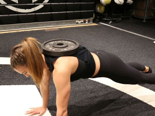 PHOTO: A Tone House trainer demonstrates a weighted push up.