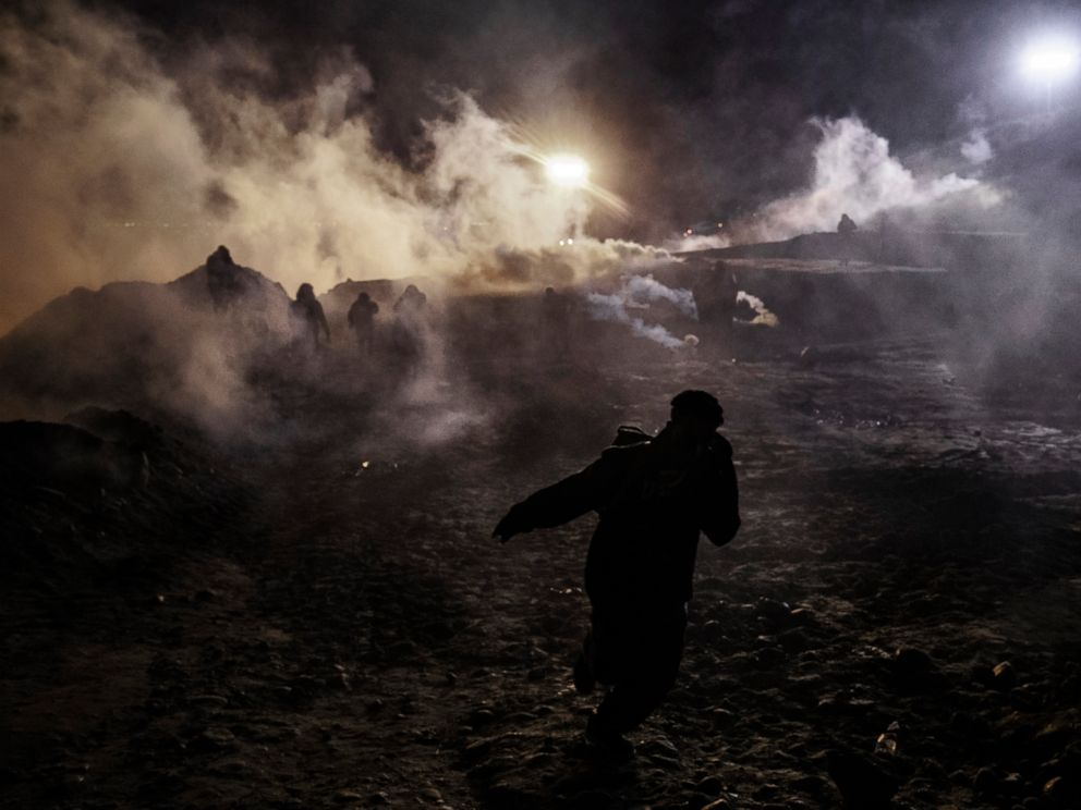 Migrants run as tear gas is thrown by U.S. Border Protection officers to the Mexican side of the border fence after they climbed the fence to get to San Diego, Calif., from Tijuana, Mexico, Tuesday, Jan. 1, 2019. Discouraged by the long wait to apply