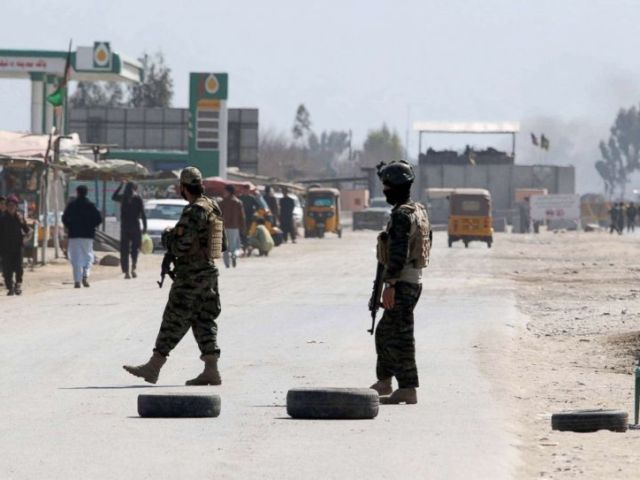 PHOTO: Afghan security officials stand guard on the road leading to the scene of a gun and suicide bomb attack in Jalalabad, Afghanistan, March 6, 2019.