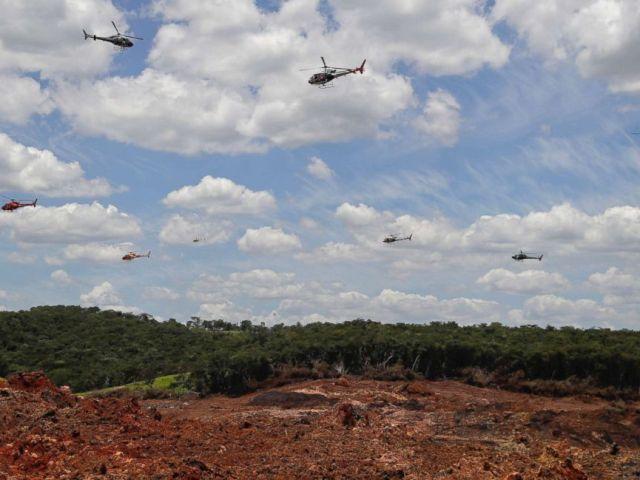 FOTO: Helikopters skuins oor 'n ysterertsmynkompleks om duisende blomblare te gee wat hulde bring aan die 110 slagoffers wat vermoor is en 238 wat nog ontbreek nadat 'n myndam 'n week gelede in Brumadinho, Brasilië, 1 Februarie 2019 ineengestort het.