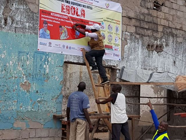 PHOTO: Workers capture an Ebola awareness poster in Tchomia, Democratic Republic of the Congo, to raise awareness of Ebola in the local community on October 9, 2018.