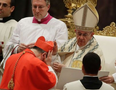 PHOTO: New Cardinal Giovanni Angelo Becciu receives the red three-cornered biretta hat from Pope Francis during a consistory in St. Peters Basilica at the Vatican, June 28, 2018.