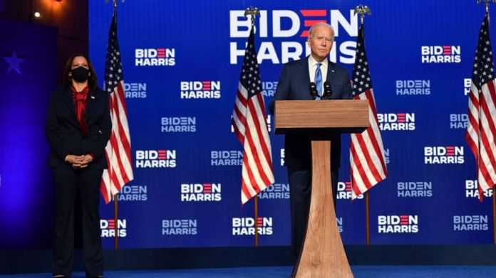 PHOTO: Democratic presidential nominee Joe Biden delivers remarks at the Chase Center in Wilmington, Del., while Sen. Kamala Harris watches, Nov. 6, 2020.
