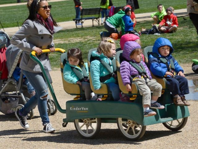 PHOTO: A daycare center employee pushes a KinderVan filled with preschool children on an outing along the National Mall in Washington, D.C., April 20, 2018.