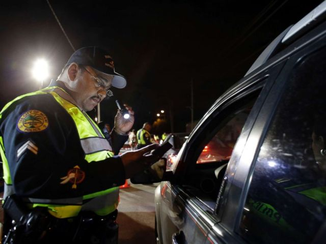 PHOTO: Miami police officer Luis Ortiz looks at a drivers license he requested from a motorist during a drunk-driving checkpoint in Miami, Jan. 29, 2015.