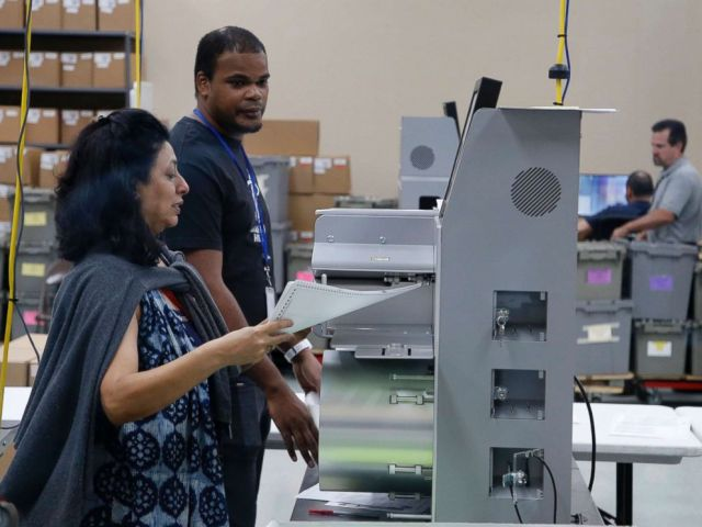 PHOTO: An elections worker feeds ballots into a tabulation machine at the Broward County Supervisor of Elections office on Nov. 10, 2018 in Lauderhill, Fla.