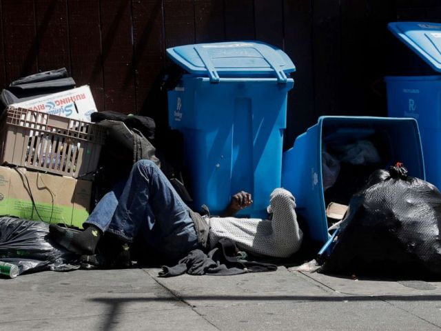 PHOTO: A homeless man sleeps in front of recycling bins and garbage on a street corner in San Francisco, Aug. 21, 2019.