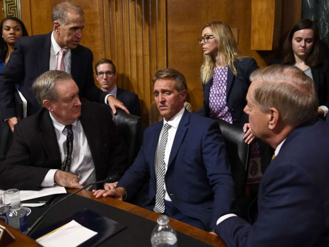 Senate Judiciary Committee member Sen. Jeff Flake speaks with committee colleagues during a hearing in Washington on Sept. 28, 2018, after requested a delay for a floor vote to allow for an FBI investigation.