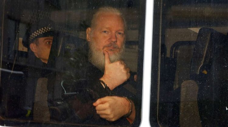 WikiLeaks founder Julian Assange is seen in a police van after was arrested by British police outside the Ecuadorian embassy in London, April 11, 2019.