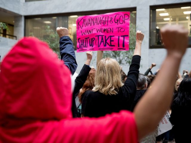 A protester of Supreme Court nominee Brett Kavanaugh wears a costume from the show The Handmaids Tale, and another protester holds up a sign that reads Kavanaugh and GOP Want Women to Shut Up and Take It in Washington, Monday, Sept. 24, 2018.