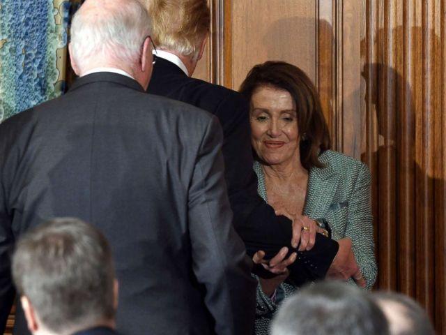 FOTO: Die Sprecherin des Hauses, Nancy Pelosi, packt Präsident Donald Trumps am Arm, als die beiden am 14. März 2019 in Washington am United States Friends of Ireland Luncheon das Kapitol passieren.