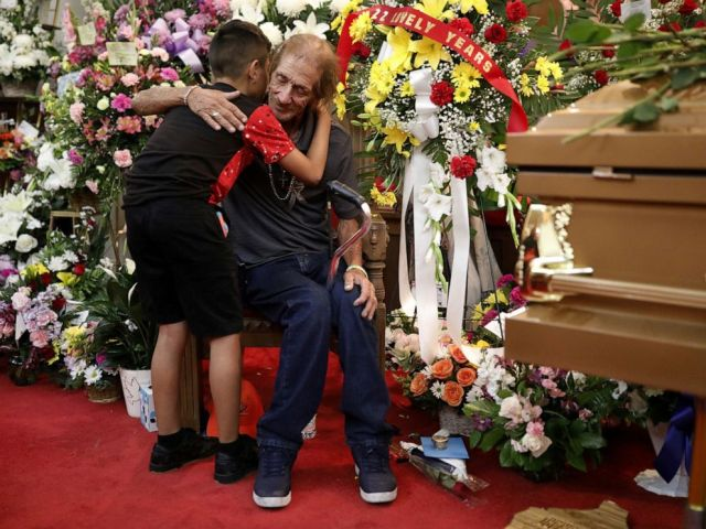PHOTO: Antonio Basco, whose wife Margie Reckard was murdered during a shooting at a Walmart store, is embraced next to her coffin at a visitation service to which he had invited the public in El Paso, Texas, on Friday, Aug. 16, 2019.