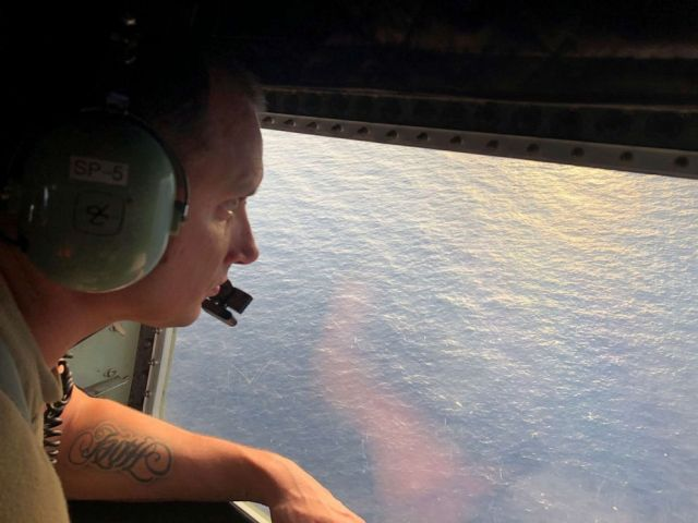 PHOTO: Tech. Sgt. Brett Corriveau, 39th Rescue Squadron loadmaster, scans the waters of the Gulf of Mexico from the inside of an HC-130P/N Combat King aircraft for any sign of the missing Airman from the 24th Special Operations Wing.