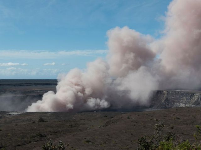 In this Friday, May 11, 2018 photo released by the U.S. Geological Survey, an ash plume rises from the Overlook Vent in Halemaumau crater of the Kilauea volcano on the Big Island of Hawaii.