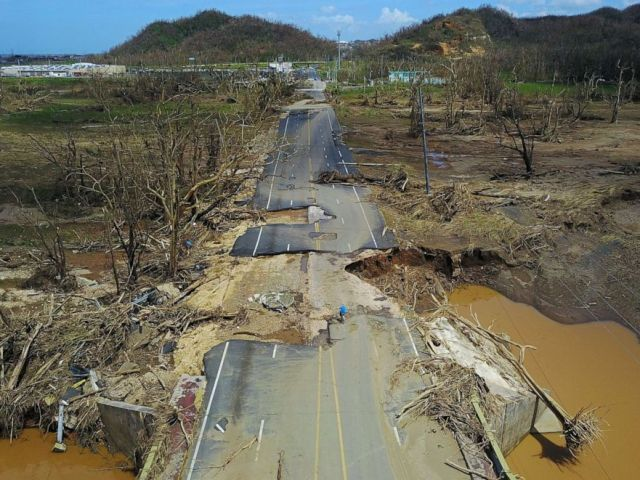 PHOTO: A man rides his bicycle through a damaged road in Toa Alta, west of San Juan, Puerto Rico, on September 24, 2017 following the passage of Hurricane Maria.