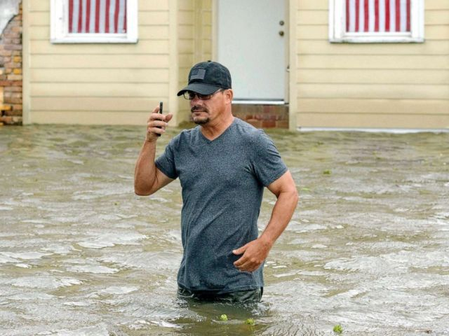 PHOTO: A man talks on his smartphone as he wades through storm surge from Lake Pontchartrain on Lakeshore Drive in Mandeville, La., as Hurricane Barry approaches, July 13, 2019.