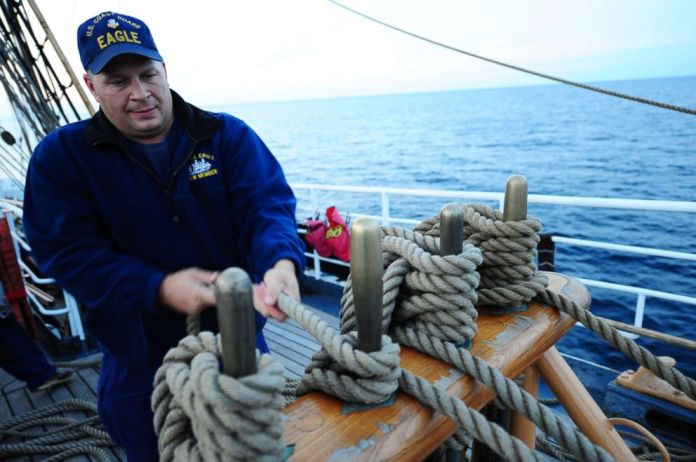 PHOTO: U.S. Coast Guard Barque Eagle crewman Petty Officer 1st Class John Presnar handles a line while adjusting sails aboard the Eagle Sept. 17, 2012.